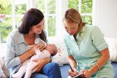 Moeder met Babyvergadering met Gezondheidsbezoeker thuis stock fotografie