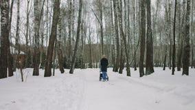 Moeder met babywandelwagen die van moederschap in de winterbos genieten stock video