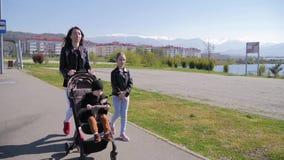 Moeder met babywandelwagen en twee jonge geitjes die een gang onderaan de straat nemen stock videobeelden