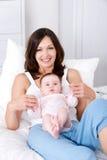 Moeder met babyzitting thuis in casuals Royalty-vrije Stock Afbeeldingen