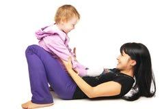 Moeder met de baby die oefeningen over wit doen stock foto