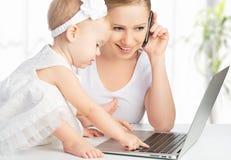 Moeder met de werken van de babydochter met een computer en een telefoon Stock Foto's