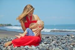 Moeder met de zitting van de babyjongen op het overzeese strand Stock Foto's