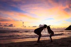 Moeder met dochter aan wal op zonsondergang royalty-vrije stock foto's