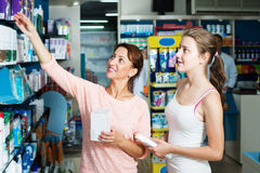 Moeder met dochter in apotheek Stock Foto