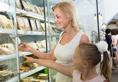 Moeder met dochter die gekoeld voedsel in supermarkt kopen royalty-vrije stock fotografie