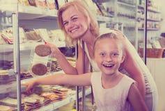 Moeder met dochter die gekoeld voedsel in supermarkt kopen stock afbeelding