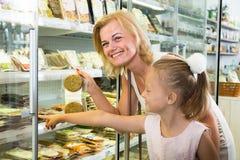 Moeder met dochter die gekoeld voedsel in supermarkt kopen royalty-vrije stock foto