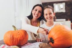 Moeder met dochter die grote oranje pompoen creëren voor Halloween royalty-vrije stock foto
