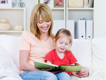 Moeder met dochter die het boek leest stock afbeelding