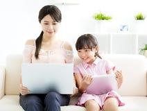 Moeder met dochter die in Laptopopbank bekijken stock afbeeldingen