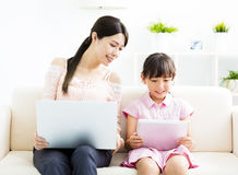 Moeder met dochter die laptop bekijkt stock afbeelding