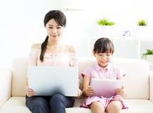 Moeder met dochter die laptop bekijkt stock afbeeldingen