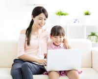 Moeder met dochter die laptop bekijkt stock foto