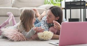 Moeder met dochter die popcorn eten en media op inhoud op laptop letten stock video