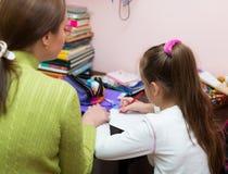 Moeder met dochter die thuiswerk doen Stock Afbeeldingen