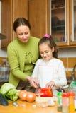 Moeder met dochter het koken bij keuken Royalty-vrije Stock Foto