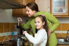 Moeder met dochter het koken bij keuken Stock Foto's