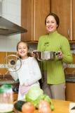 Moeder met dochter het koken bij keuken Stock Afbeeldingen