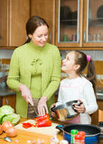 Moeder met dochter het koken bij keuken Stock Fotografie
