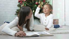 Moeder met dochter het liggen op de vloer en het lezen van een boek dichtbij Kerstboom stock videobeelden
