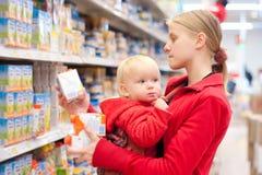 Moeder met dochter het winkelen in supermarkt stock afbeeldingen
