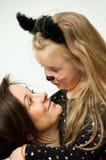 Moeder met dochter in katjeskostuum Stock Fotografie
