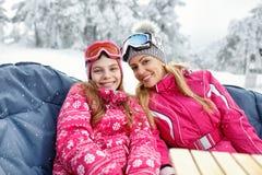 Moeder met dochter op het ski?en zitting in koffie Stock Afbeeldingen