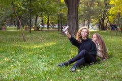 Moeder met dochter zeven jaar oud in de herfstpark bij zonsondergang Stock Foto's