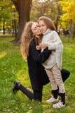 Moeder met dochter zeven jaar oud in de herfstpark bij zonsondergang Stock Fotografie