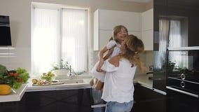 Moeder met dochterpret het spinnen rond zich thuis in de keuken De mooie vrouw in een lichte kleding heft haar op stock footage