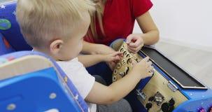 Moeder met een kleine zoonsspelen met een houten autostuk speelgoed Kinderen` s onderwijsspeelgoed stock footage