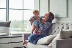 Moeder met een zitting van de 8 maand oude baby op een bank thuis stock fotografie