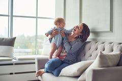 Moeder met een zitting van de 8 maand oude baby op een bank thuis royalty-vrije stock fotografie