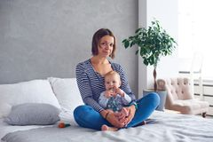 Moeder met een zitting van de 8 maand oude baby op een bed thuis stock foto
