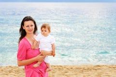 Moeder met haar baby bij strand Royalty-vrije Stock Foto