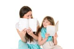 Moeder met haar boek van de dochterlezing royalty-vrije stock afbeelding