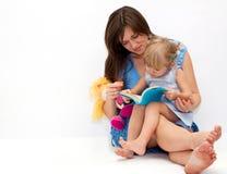 Moeder met haar dochter die een boek leest stock afbeelding