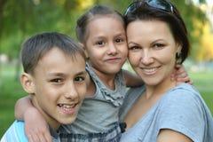 Moeder met haar kinderen in de zomerpark stock foto's
