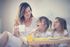 Moeder met haar kleine dochters die ontbijt in het bed hebben Stock Afbeeldingen