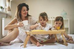 Moeder met haar kleine dochters die ontbijt in het bed hebben Mo Stock Afbeeldingen
