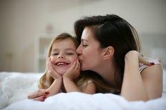 Moeder met haar leuke kleine dochter die op bed liggen Stock Fotografie