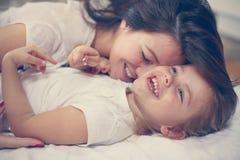 Moeder met haar leuke kleine dochterzitting op bed stock afbeeldingen