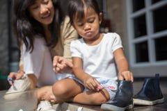 Moeder met haar peutermeisje die hun schoenen samen wassen stock foto's