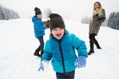 Moeder met haar twee zonen buiten het spelen in de sneeuw stock fotografie