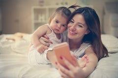 Moeder met haar weinig baby die pret in het bed hebben Moeder het maken royalty-vrije stock afbeeldingen
