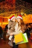 Moeder met haar weinig dochter in de hoed van de rode Kerstman Stock Afbeelding
