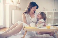 Moeder met haar weinig dochter die ontbijt in het bed hebben stock foto