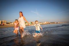 Moeder met haar zonen die op de kust spelen stock afbeelding