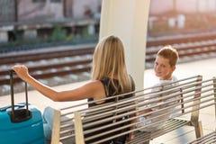 Moeder met haar zoon die op een trein op station wachten stock foto's